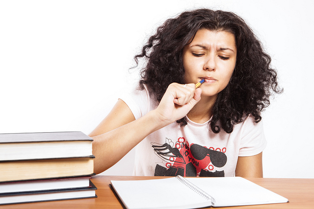 A girl writing and thinking about her examination