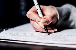 The image of a student doing homework (writing in notebook)